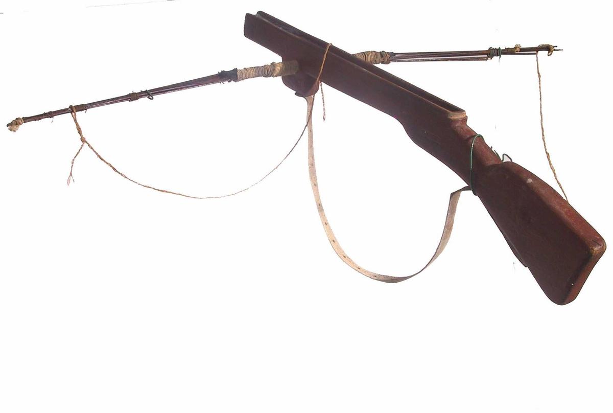 Form: Gevær-fasong, med jernspiler satt inn på tvers et stykke foran midten. Skulderrem i lær, løsnet i ene enden. Snor til å spenne pil med er festet ytterst i spilene, røket på midten. Pil-liknende ammunisjon.