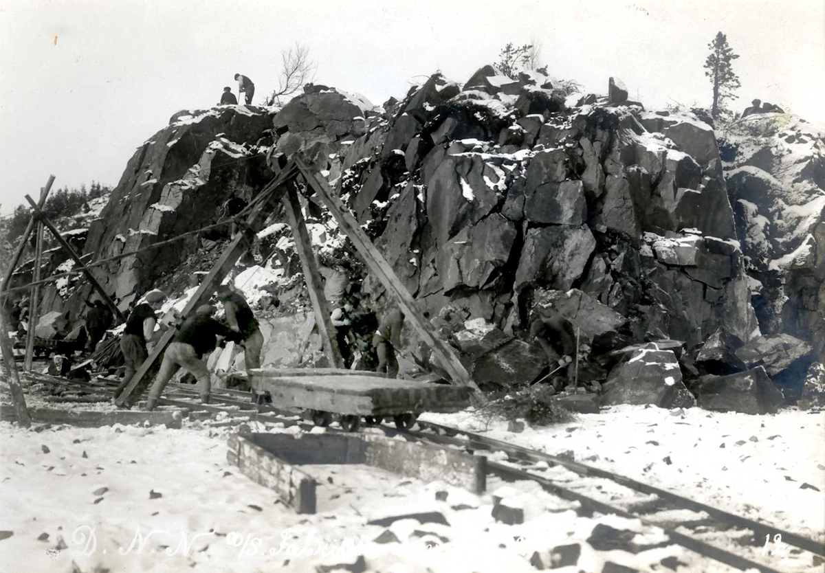 """""""03/12-1912"""" Nitriden. Utsprengning og planering av fabrikktomten. Stubbebrytere (heisanordning), tralle og skinnegang for borttransport av stein. To personer på toppen utfører handboring i fjellet."""