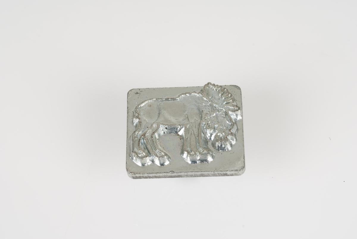 Stempel av metall/jern. Stempelen viser et bilde av en elg. Påført tekst på baksiden av stempelet.
