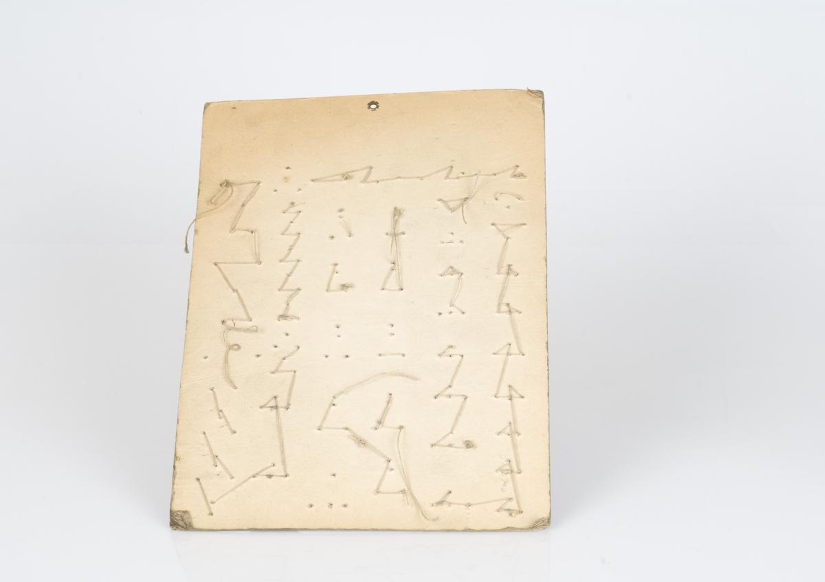 En prøveplate med forskjellige typer beltespenner påfestet på platen. Beltespennene er av metall. Antall beltespenner på platen er 39. Påført tekst på platen.