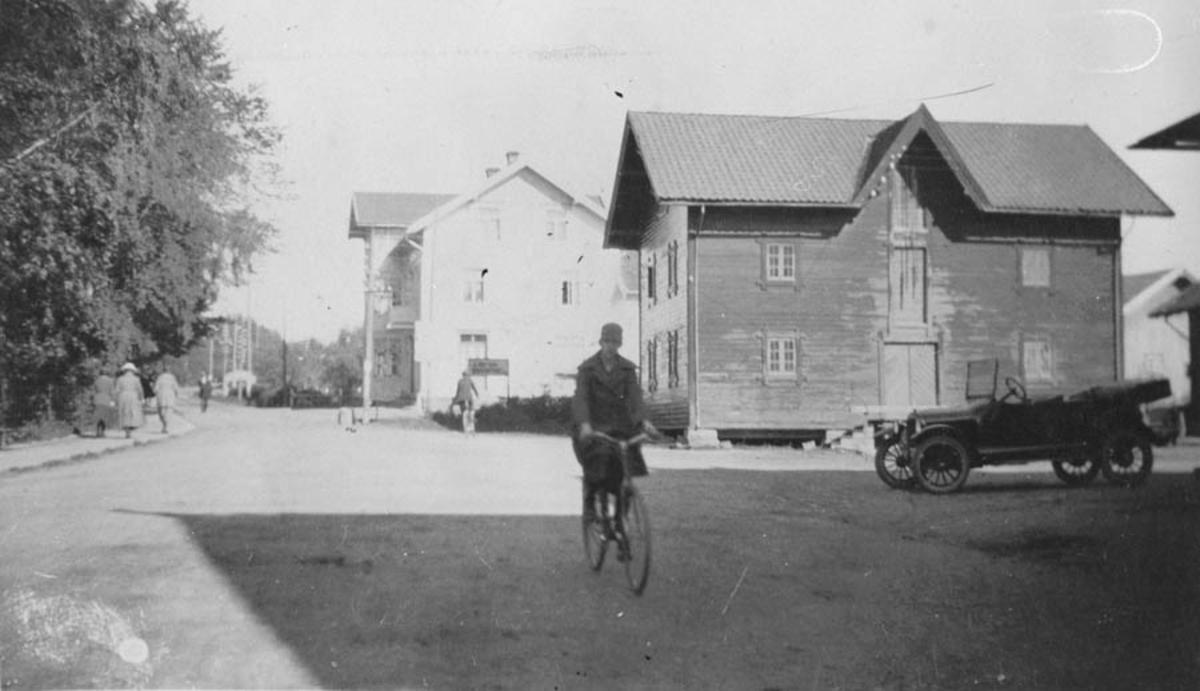 Bilde av en bil, (T-Ford). Dame på sykkel.