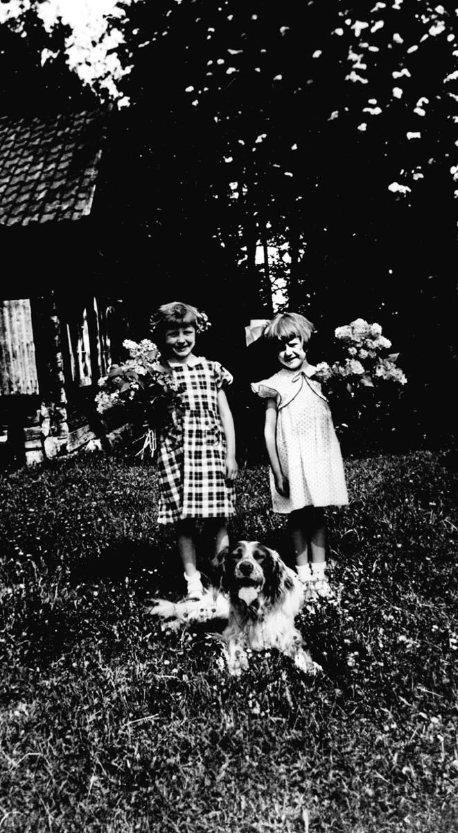 To piker med store blomsterbuketter. Hund foran i gresset.