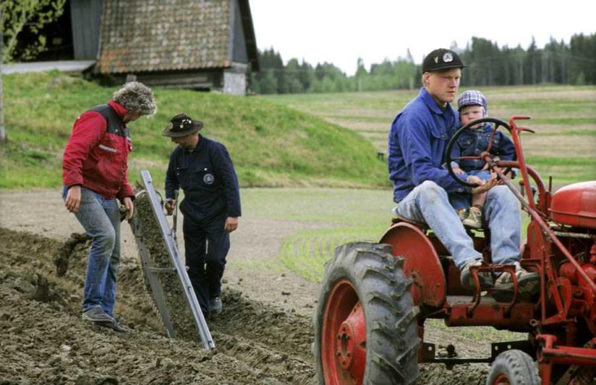 """Dokumentasjon av drenering i forbindelse med åpning av ny utstilling: """"Jordbrukets utvikling på Romerike"""" på Gamle Hvam. Bruk av dreneringsredskaper. Demonstrering av drenering. Mann (Christoffer Hønsen) og gutt på traktor, to menn går bak (mann med hatt er trolig Øyvind Kværner)"""