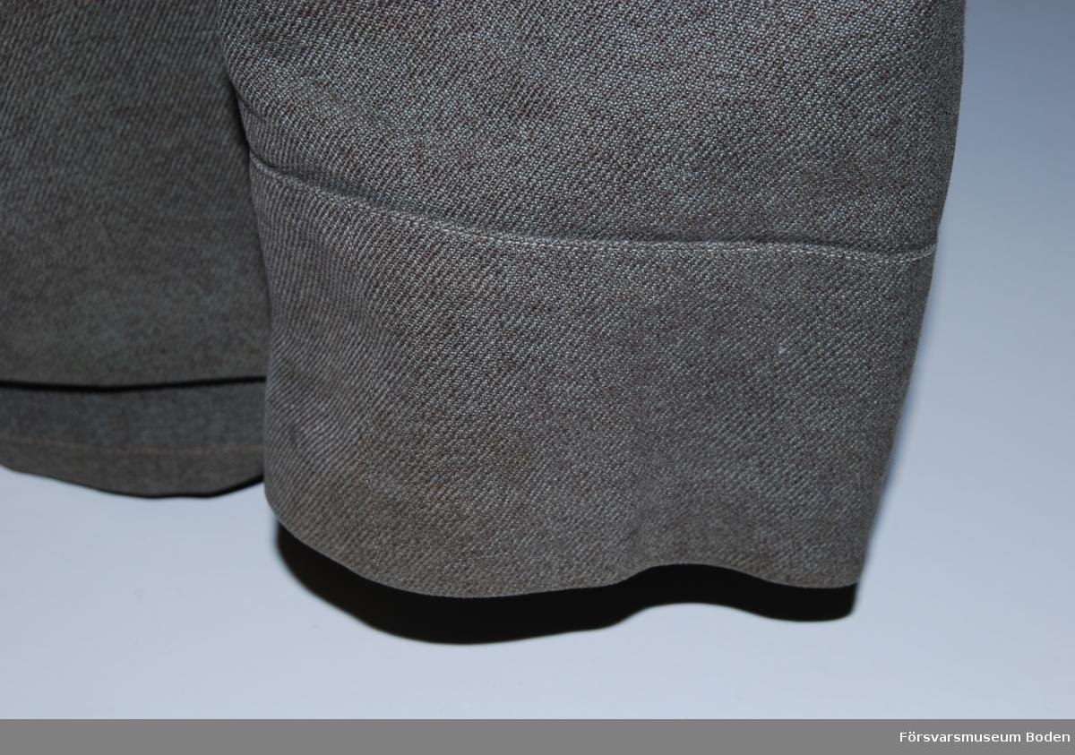Gråbrungrönt linnetyg utan fodring. I övrigt lik m/1923 med ståndkrage och fyra utanpåliggande fickor med raka lock och dolda knappar. Extra tryckknappar vid lockens kanter. Framtill sex gråfärgade knappar av fortifikationens modell, och två knappar på ryggen vid midjan.. Likadana knappar modell mindre upptill på de fasta axelklaffarna. Nertill på dessa bokstaven J av svart kläde betecknande ingenjörtrupperna. Tre metallstjärnor i silver på vardera sidan av kragen betecknande kapten. Ärmuppslag med söm.