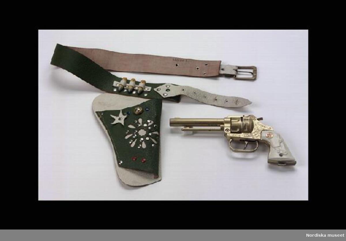 """Inventering Sesam 1996-1999: Revolver L 21 cm, B 2 cm, H 7,5 cm Bälte L 81cm, B 4 cm Hölster L 24 cm. Patroner 3,5 cm, Diam 1 cm Revolver med bälte, hölster och 3 patroner Revolver: gjuten i metall i två delar. Gulbronserad. Slät pipa, stock med dekorslingor, varbygel vid avtryckaren, kolven täckt på sidorna av vit plast med hästhuvud. Vid laddning spänner man ut hanen och tar bort spärren på höger sida, då öppnas pistolen och man kan ladda med en rulle knallpulver som fästs på den lilla piggen bakom cylindern och läggs i banan bakom piggen, så att när man trycker på avtryckaren slår hanen på knallpulverremsan. När man skjuter skall knallpulverremsan matas upp automatiskt vid hanen.  Revolvern märkt: på sidorna av stocken """"LONE STAR"""". Mellan pipa och stock """"PAT. NO 677227"""". Vid cylindern (syns när den är öppen) """"DCMT / LTD / SLIKKA TOY / MADE IN / ENGLAND"""" DCMT står för Diecast Casting Machine Tools Ltd. Se vidare """"Millers Toys and Games Aniques Checklist"""" av Hugo Marsh, London 1995, sid 124. Bälte och Hölster: av läder, grön och vit. Spänne av metall. Hölster fäst vid bältet med nitar, hölstret dekorerat med nitar i rött, blått och silver. Ovanför hölstret tre hållare i läder för patroner. Patroner: tre stycken av trä, gulmålade, spetsen i silver. Leif Wallin 1996"""