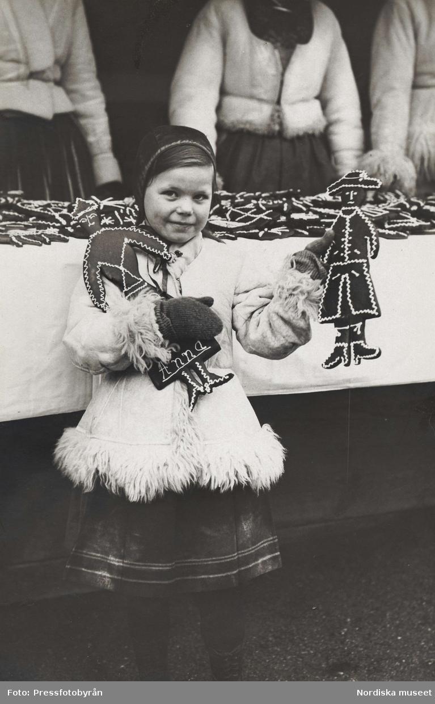 Flicka (Maj Lister) med pepparkakor i händerna. Skansens julmarknad 1923.