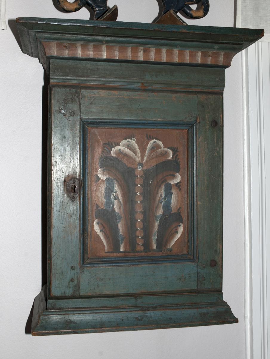 Hängskåp av trä med profilerat över- och understycke, målat blågrönt med dekor av dalatyp på dörrspegeln i brunrött, svart, blått och vitt, och röd och vit bård på överstycket. Invändigt två hyllor och en liten hylla.