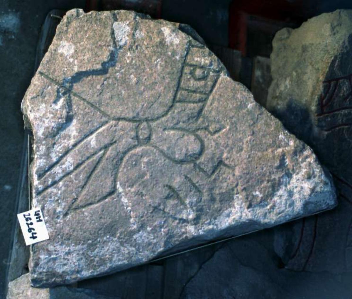 Tre fragment av runsten, av ljusröd, medelkornig granit. Kvarsittande medeltida bruk visar att fragmenten använts som byggnadsmaterial. 1. Runristat fragment av ljusröd, grovkornig granit, storlek 65 x 22 cm, tjocklek 40 cm. Runornas höjd 6 - 7 cm. Fragmentet har, enligt Gustavson (Fornvännen 1977) sannolikt utgjort en del av vänstersidan i en runsten. Kvarsittande medeltida bruk visar att fragmentet har använts som byggnadsmaterial. Inskrift: ... stain eftir... (sten efter). 2. Runristat fragment av ljusröd, medelkoring granit. Storlek 50 x 47 cm, tjocklek 43 cm. Runornas höjd 5 - 7 cm. Kvarsittande medeltida bruk visar att fragmentet har använts som byggnadsmaterial. Inskrift: ....-bur sin... (sannolikt broder sin). 3. Runristat fragment av rödaktig granit. Mått: 29x11 cm. runhöjd 6,5 cm. Inskrift: ...ih....