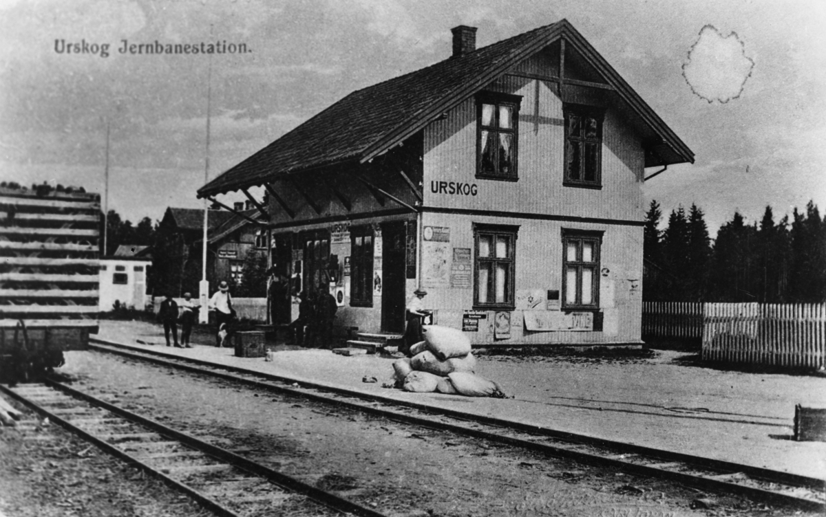 Urskog stasjon. Reisende og gods venter på toget.