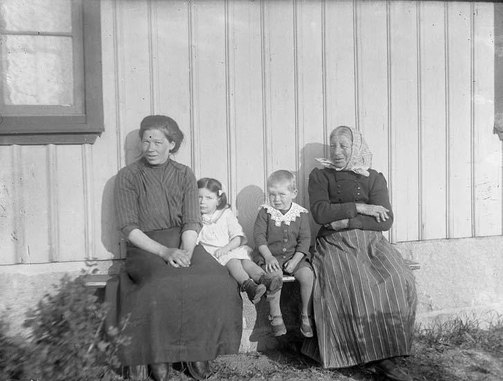 """Enligt notering: """"Två kvinnor, två barn vid husväggen""""."""