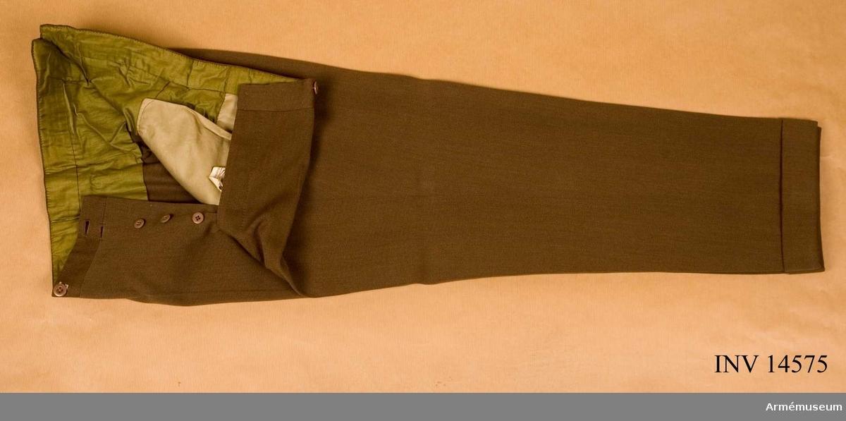 Grupp C I. Byxor av khakidiagonalkläde, långa. På framsidan sprund med fem bruna benknappar och sex st dito för hängslen. Foder av grönt tyg. På byxorna nedre del finns ett 4,5 cm brett veck. Byxorna har fickor på vardera sidan.