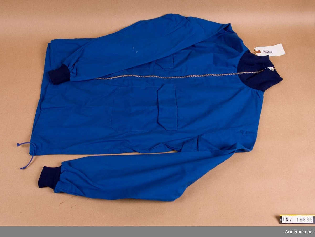 Sydd i blå poplin. Har två påstickade bröstfickor med kard- borrfäste, insydd ficka med blixtlås samt ärmmuddar och krage av trikå i mörkblå färg. Blusen är blixtlåsförsluten mitt fram samt dragsnöre i nederkanten för reglering av vidden. Storlek 4.Träningsblusen används av all militär personal i fredstjänsten.