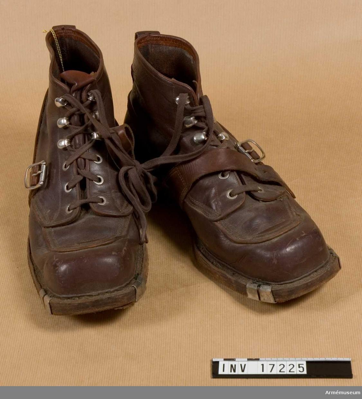 """Grupp C I.  Av brunt läder med breda spetsar och med järnbeslag vid skidremmar. Ovanpå vristen finns en rem med spännen för att kängorna ska sitta fast på fötterna. Kängorna bindes fast med snören. Klacken är betäckt med gummi. På sulorna står """"44 A"""" - storleksnummer."""