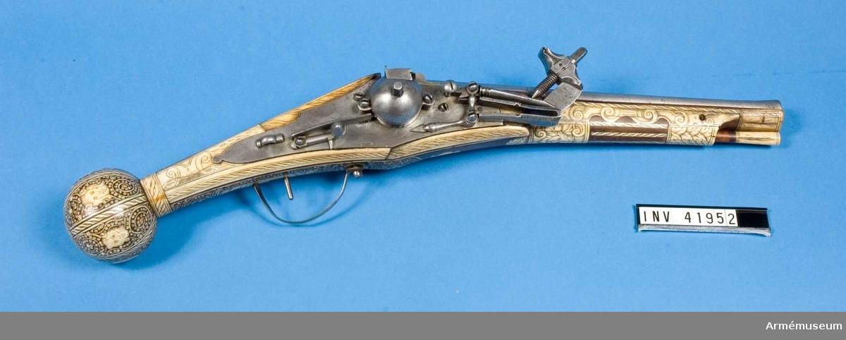 """Grupp E III. Hjulåspistol, 1500-talets senare hälft, Tyskland.  Lika med och i par med AM.041951.   Pipan har åttakantiga kammarstycken med ett ingraverat """"L"""". Därefter rundad och vidgar sig något vid mynningen.  Den bruna stocken är rikt inlagd med graverat hjorthorn. Den stora kolvkulan har likaledes inläggningar med hjorthorn, föreställande en mansperson med horn i pannan och på kolvkulans undersida finns en krigare iförd hjälm. Pistolen har bälthake.  Ävenledes i gott skick, men en skena nedanför låset lös och bakom låset finns en spricka."""