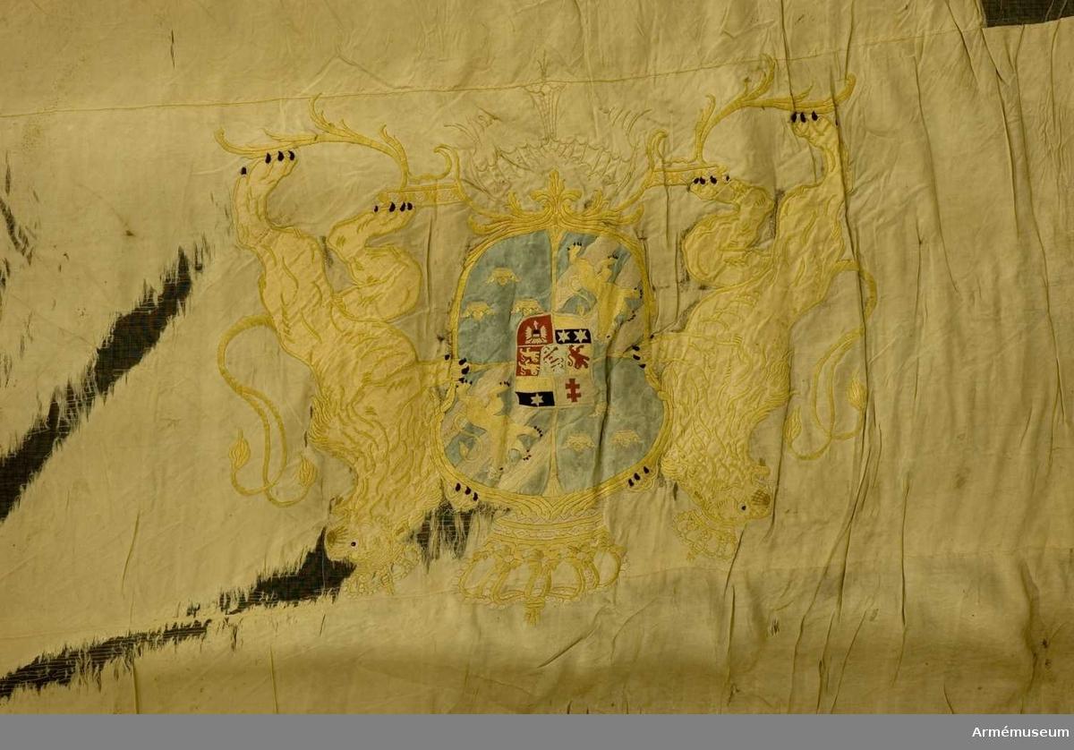 Duk: Tillverkad av enkel vit sidenkypert, sydd av tre horisontella våder. Duken kantad med ett vitt band. Samma sorts band som tennlickorna, en rad, är fäst mot.   Dekor:  på mittvåden broderat och applicerat lika på båda sidor, stora svenska riksvapnet under Fredrik I, (Hessens hjärtvapen), i siden och silke. Skölden bildad av från postamentet utgående ornament, krönt av sluten krona, hållen av utåtseende, dubbelsvansade med slutna kronor krönta lejon, i hörnen kronor liknande riksvapnets. Riksvapnet i applikation i ljusblå kypert. Hjärtvapnet i läggsömsbroderi i rött, svart och blått. Postamentet applicerat i gul kypert, broderade med gult silke. Lejonens kronor i gult och vitt silke. Kronorna i hörnen i dubbelsidig plattsöm.  Stång av vitmålad furu. Holk av förgylld mässing.   Anmärkning: Duken mycket trasig. Ytterkanten med hörnkronorna bortsliten, uppfodrad på tyll. Spets saknas. Livfanan olik den oftast förekommande.
