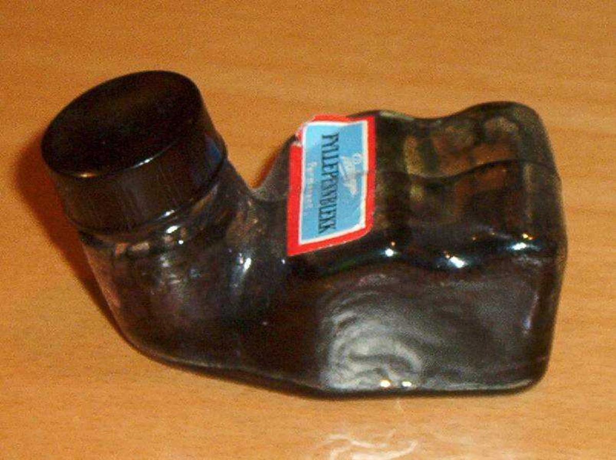 Liggende liten glassflaske med flat underside. Med skrukork og blå og rød etikett.