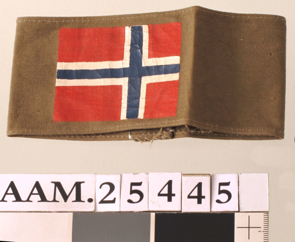 Bånd i jordgrønn farge, med påmalt norsk flagg.
