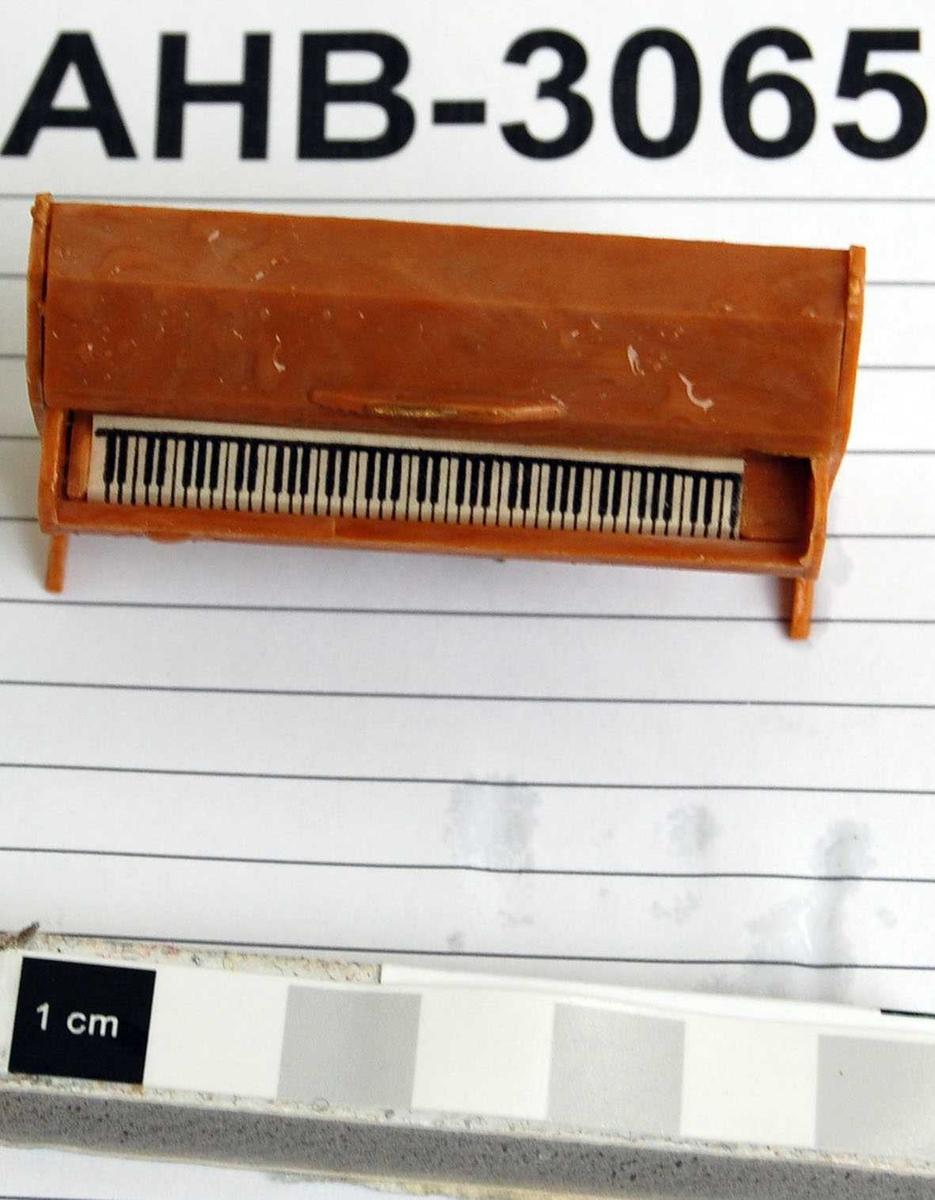 Piano med mange detaljer. Lokket over klaveret og topplokket er bevegelig. Strenger og mekanikk er antydet med gullmalt plast. Klaviatur trykket på en papirremse. Pedalene er brettet ut fra hovedformen og malt svarte.