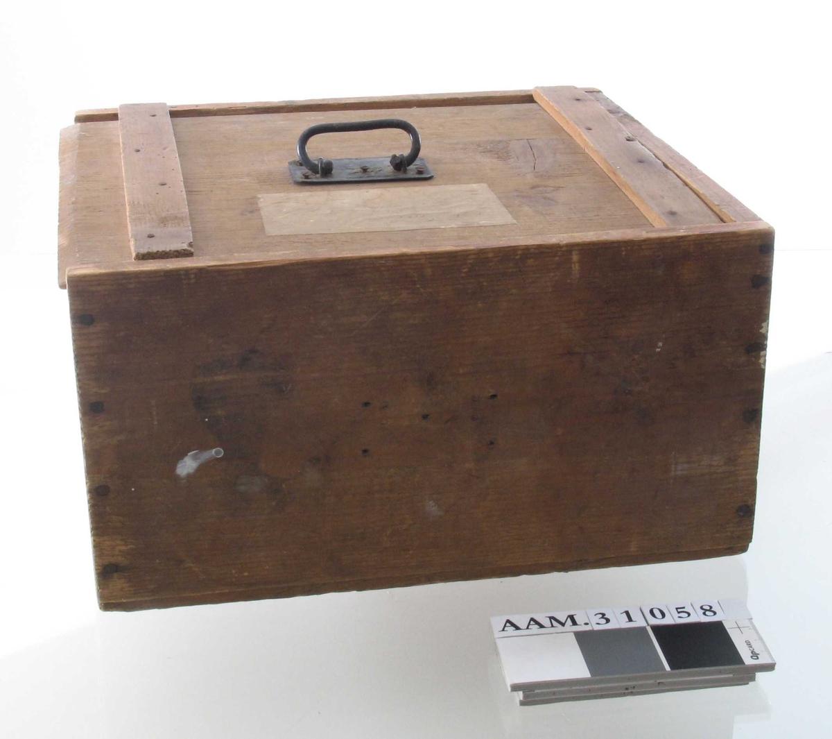 Liten maskin med håndsveiv, montert på plate av stein (?). Oppbevart i tilpasset trekasse med skyvelokk og håndtak.
