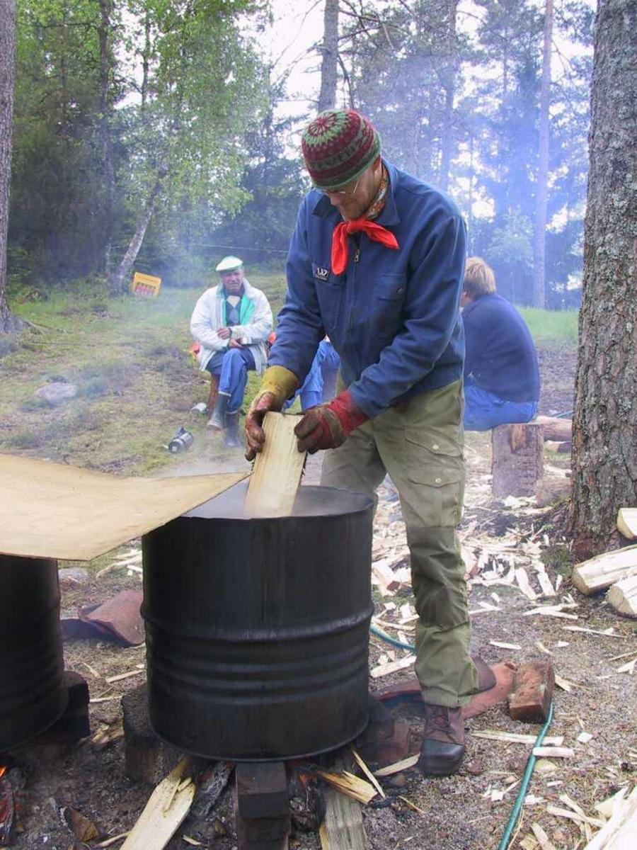 Spontekking på Iveland bygdemuseum. Steven Carpenter koker sponene. Oljefat som kokekar.