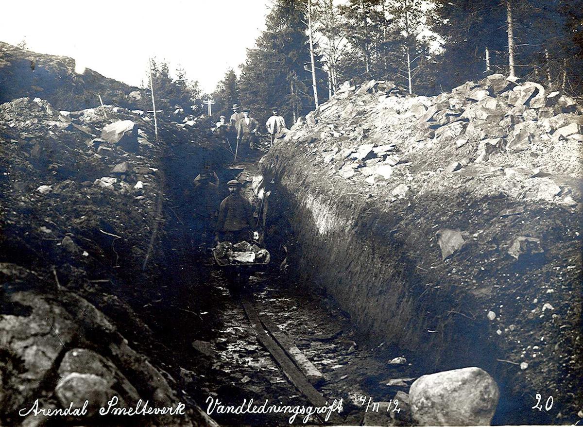 """""""04/11-1912"""" Nitriden. Smelteverket. Vannledningsgrøft for tilførsel av drikkevann til bedriftene fra Ulfsryggtjern og Stemtjern. Planker for kjøring av trillebår av tre med jernhjul. Dype grøfter."""