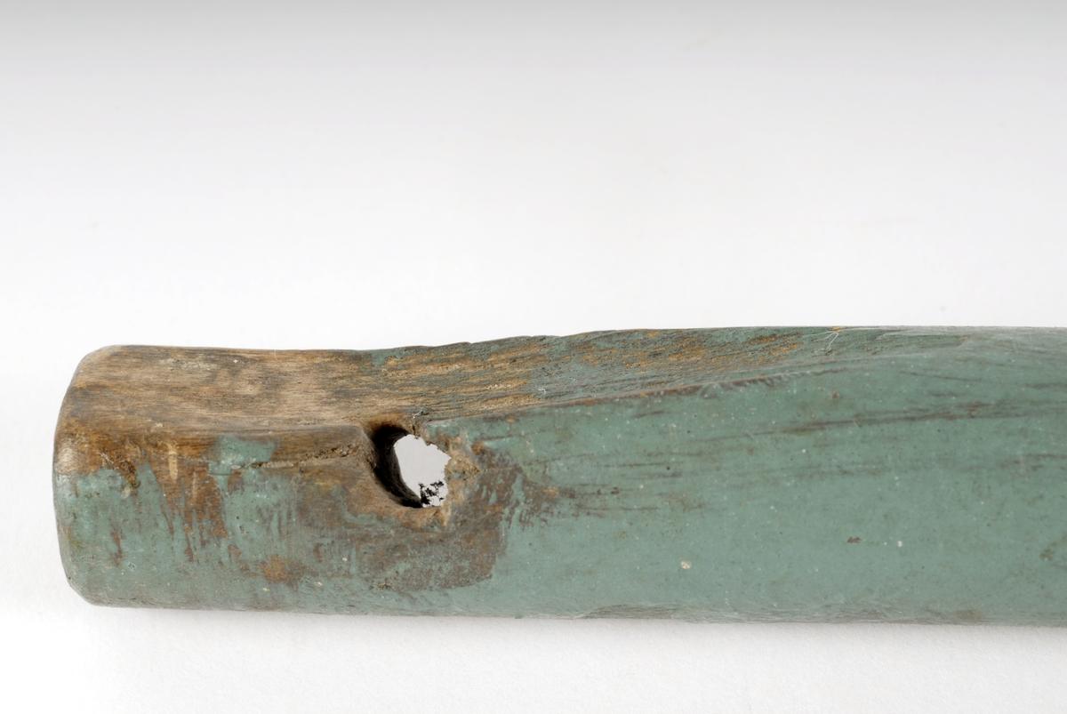 Dreid hode øverst med flere vulster, flatet, slisse for veiv på rokkehjulet. Hull nederst for lærreim, som skal forbinde den med trøa.