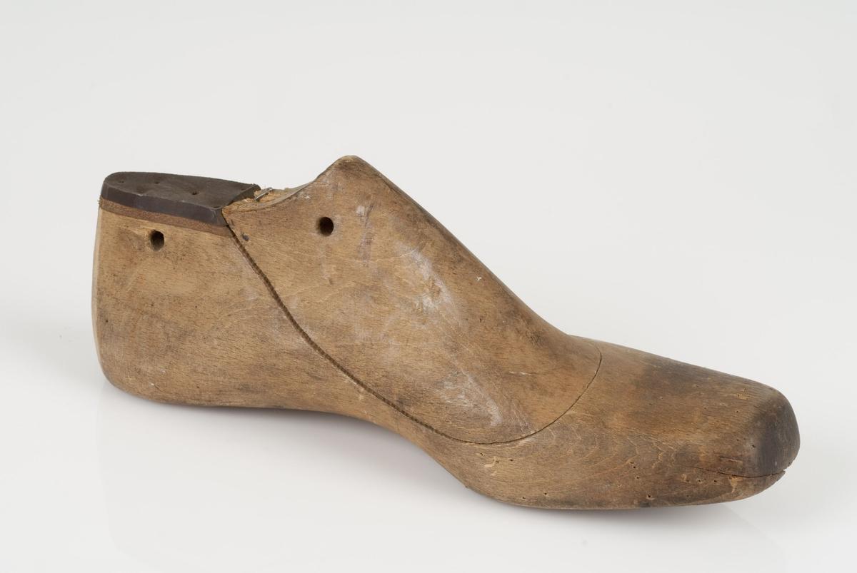 En tremodell i to deler; lest og opplest/overlest (kile). Venstrefot i skostørrelse 43, og 8 cm i vidde. Lestekam i skinn med logo.