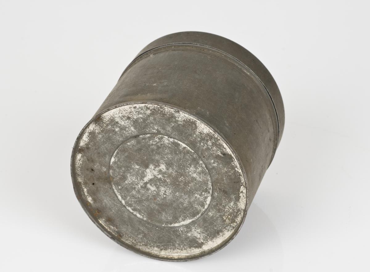 Rund metallboks med lokk. Boksen er tom.