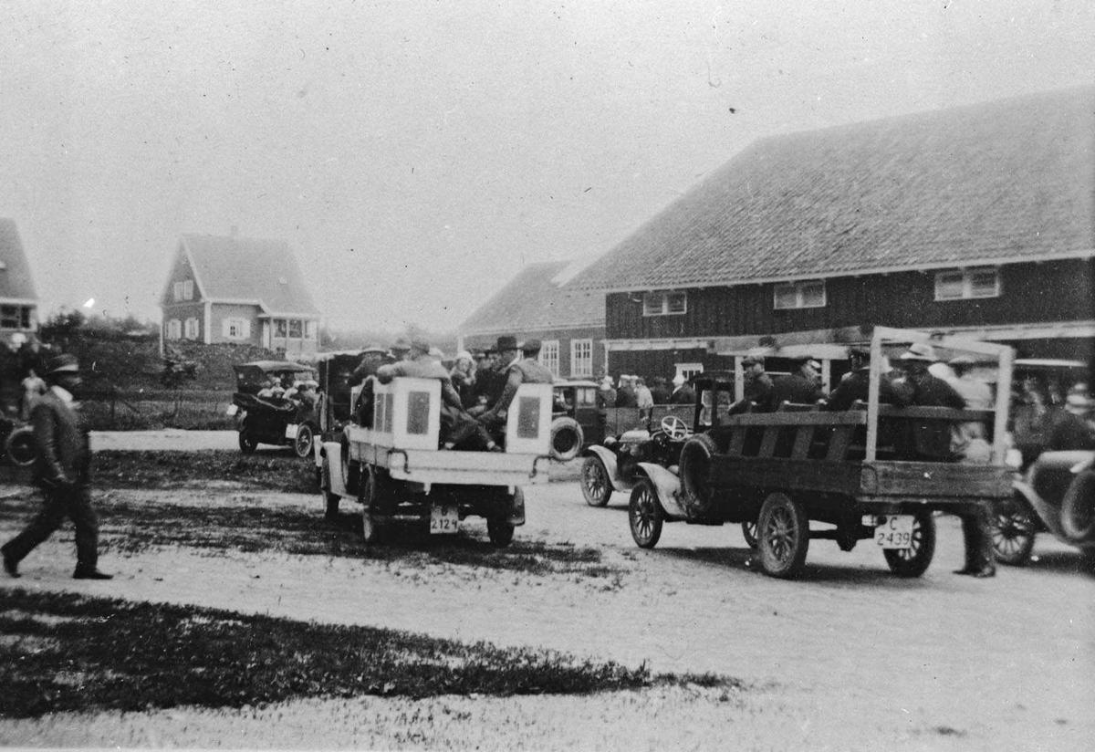 Bikongressen i Ås, juli 1927. 2 lastebiler innrettet for persontransport samt personbiler på et gårdstun. To villaer i bakgrunnen.