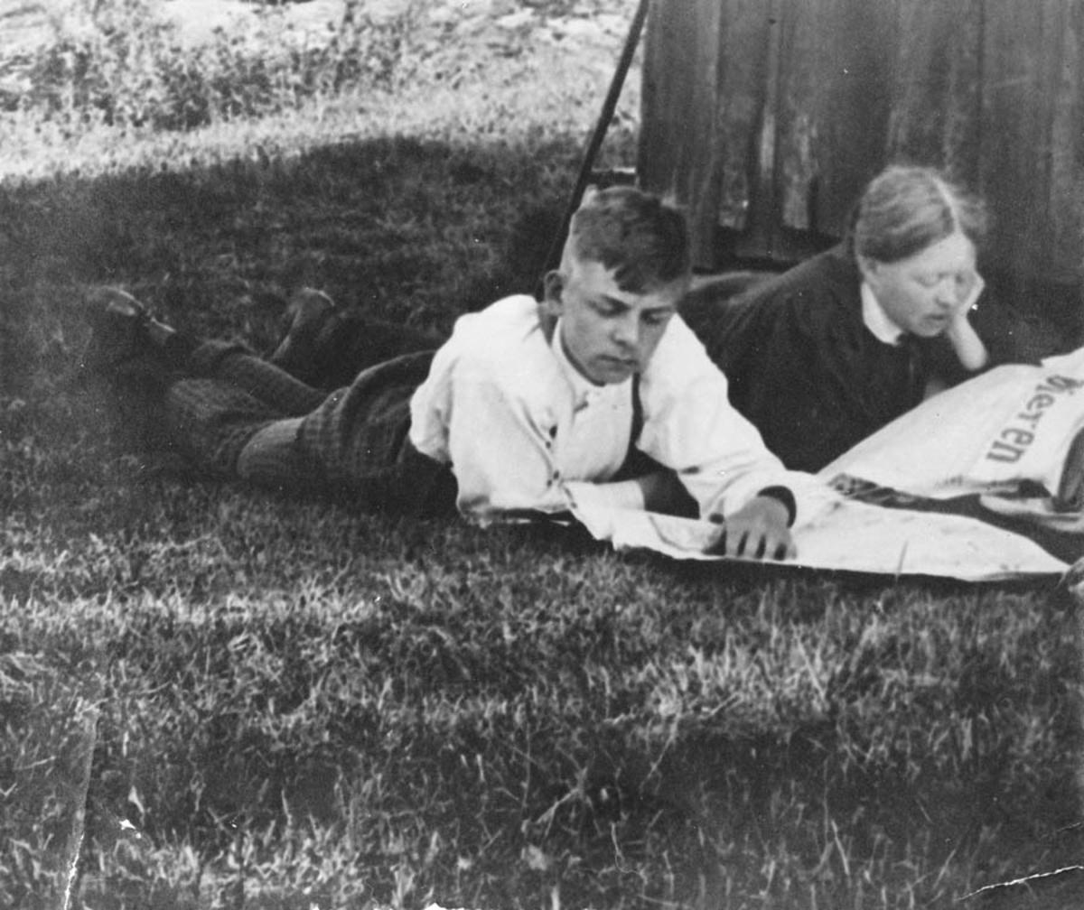 Jorulf Bjørnstad og hans mor Inger Johanne Bjørnstad, leser avisen liggende i skyggen på gresset.
