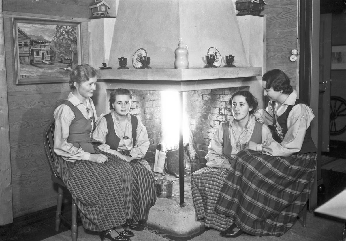 Fire jenter ved peisen.