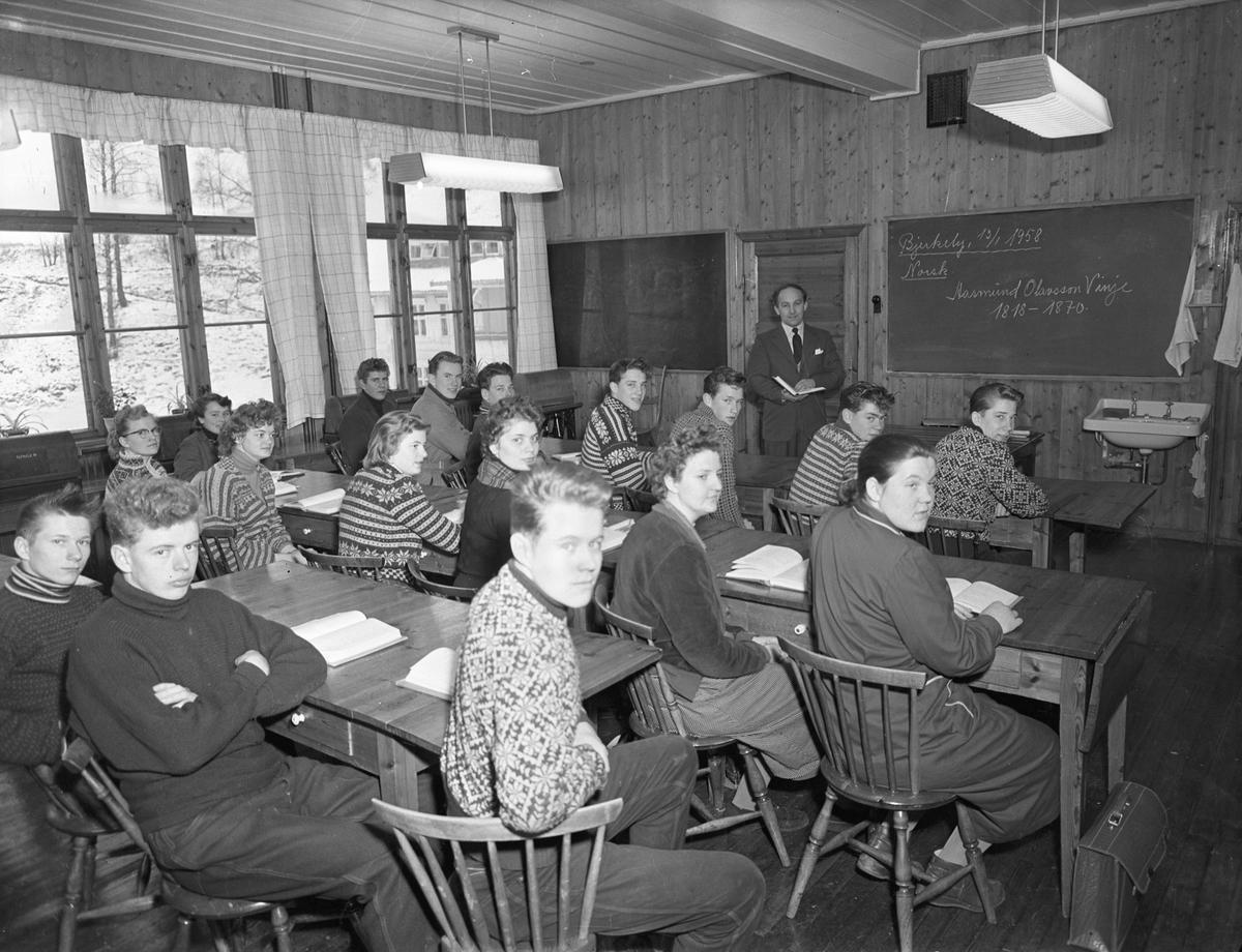 "Bjerkely. Klasserom. På tavla står det ""Bjerkely, 13.01.1958. Norsk. Aasmund Olavsson Vinje 1818-1870"""
