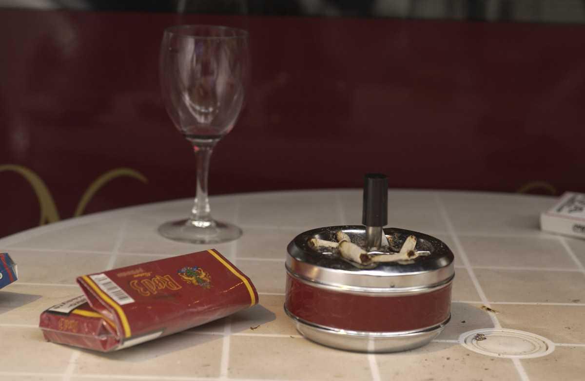 """Utebord med tobakkspakke, sigarettpapir """"snurre"""" askebeger m. sneiper, tomt vinglass & tom IFA pastilleske."""