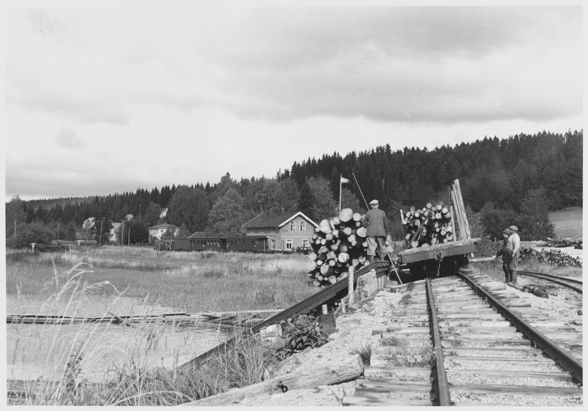 Tømmervelting fra jernbanevogn på Skulerud brygge. Sporet er jekket opp for at tømmerbunten lettere skal velte av vognen.