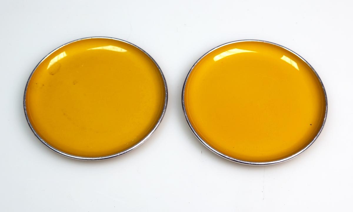 To like asjetter, trolig som underlag for kopper og glass, som er gulmalte og har gyllen kant.  Materialet har en glassaktig lyd og er lett, men har en overflate som ser mer ut som emalje eller malt metall.
