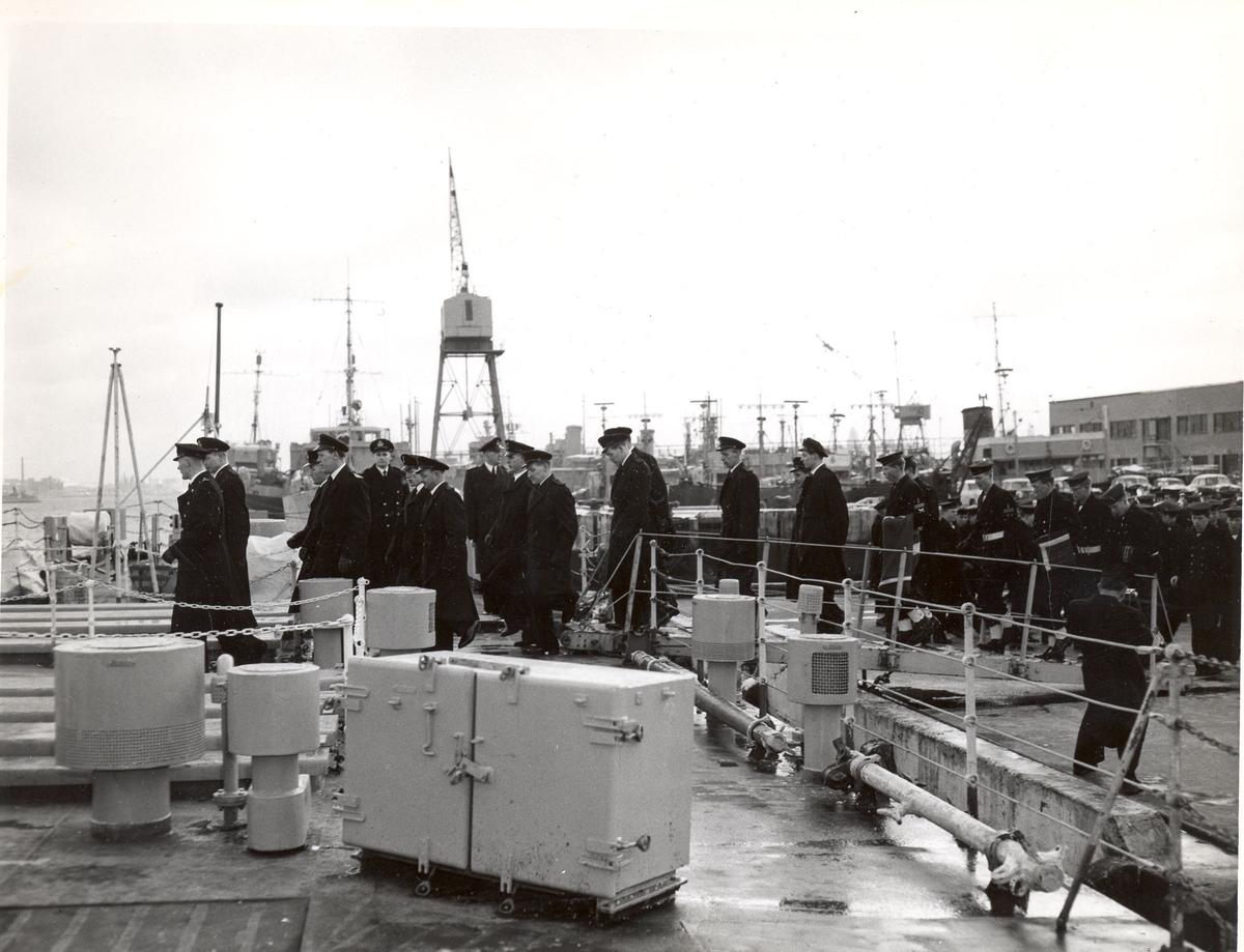 """Overtakelsen av River-kl.fregatt KNM """"Draug"""", ex. HMCS Pentang 25. januar 1956. Det norske mannskapet marsjerer om bord i KNM """"Draug"""" før kommandoen heises."""