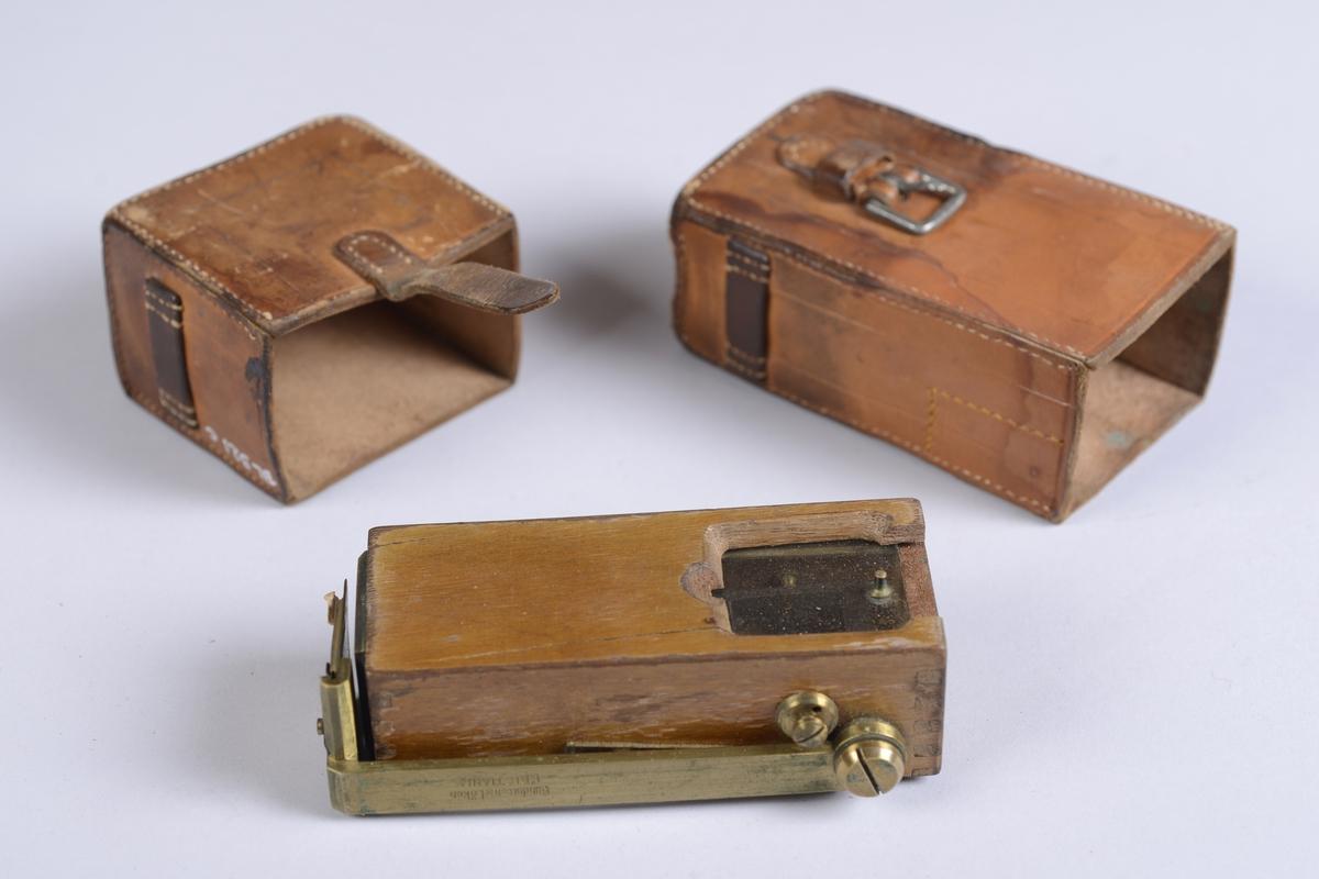 Måleinstrument oppbevart i rektangulært etui av skinn. Etuiet har reim og metallspenne for feste av lokket på front, og hemper på sidene.  Selve treesken:  10*3*4 cm.  Lengde på messingdelen:  10 cm.  Bredde på messingdelen:  1 cm.  Messingskiva fremme:  3*3 cm.  Etuiet:  6*10,5*4 cm.  Etui-lokket:  4,5*5,5*6,5 cm.