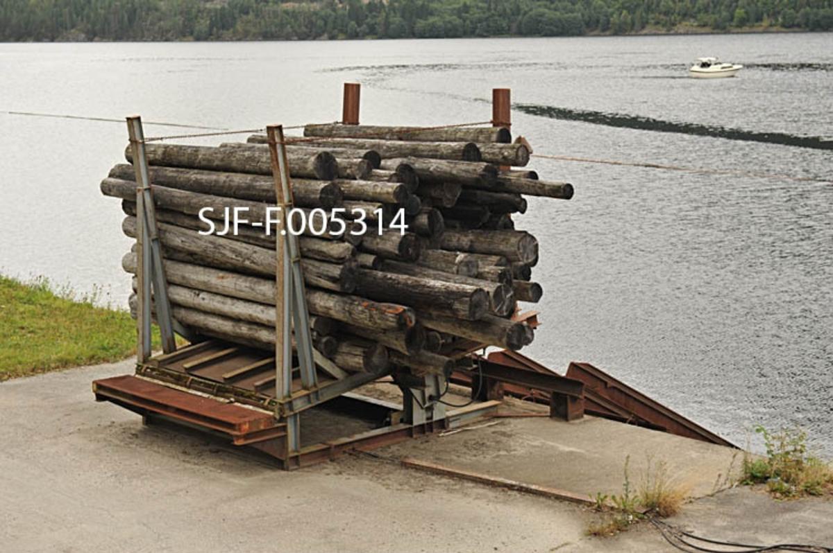 Utislagsplass med tømmermålingsfasiliteter ved Dalen i Tokke i Telemark.  Anlegget ligger like øst for tettstedet, ved den såkalte Lasteinsvingen.  Her er det bygd en veg langs stranda mot Bandak.  Mellom denne vegen og skråningen ned mot vatnet er det plassert ei ei «vogge», et stativ som tømmerlassene ble veltet over i fra bilene.  Her ble tømmeret buntet («klubbet»).  Så kunne stengene på sida mot sjøen løsnes.  Deretter ble den bakre (indre) delen av vogga hevet ved hjelp av hydrauliske heisemekanismer, slik at tømmerbuntene («klubbene») skled via kraftige stålbjelker på den bratte strandskråningen og ned i vatnet.  Anlegget omfattet også ei inspeksjonsrampe for lassmåling av tømmer og ei kontorbrakke for tømmermålere, som ikke er med på dette bildet.   På Bandak, like utenfor utislagsstedet, ble tømmerbuntene bundet sammen i slep, som ble trukket over Vestvannene (Bandak, Kviteseidvatn og Flåvatn) med slepebåt.  Fram til cirka 1980 ble tømmeret fløtet videre ned gjennom sluseanleggene Bandak-Norsjøkanelen, over Norsjø, og via Løveid sluser til Skien.  Fra da og fram til tidlig på 2000-tallet ble tømmeret fra Vest-Telemark tatt opp ved Kåsa, like ovenfor det øverste sluseanlegget (Hogga), og kjørt videre med lastebiler.  De første forsøkene med utislag fra brygge ved Dalen ble gjort like etter 2. verdenskrig.  Etter at den nye kraftstasjonen ved Dalen ble satt i drift i 1961 ble slik levering det normale for tømmer fra Tokkevassdragets nedslagsfelt.  Lassmåling av tømmer («FMB-måling») ble innført i Norge – antakelig også i Vest-Telemark – tidlig i 1970-åra.  Denne målemetoden ble i hovedsak brukt på slipvirke, altså lavkvalitetsvirke som skulle til treforedlingsindustrien.