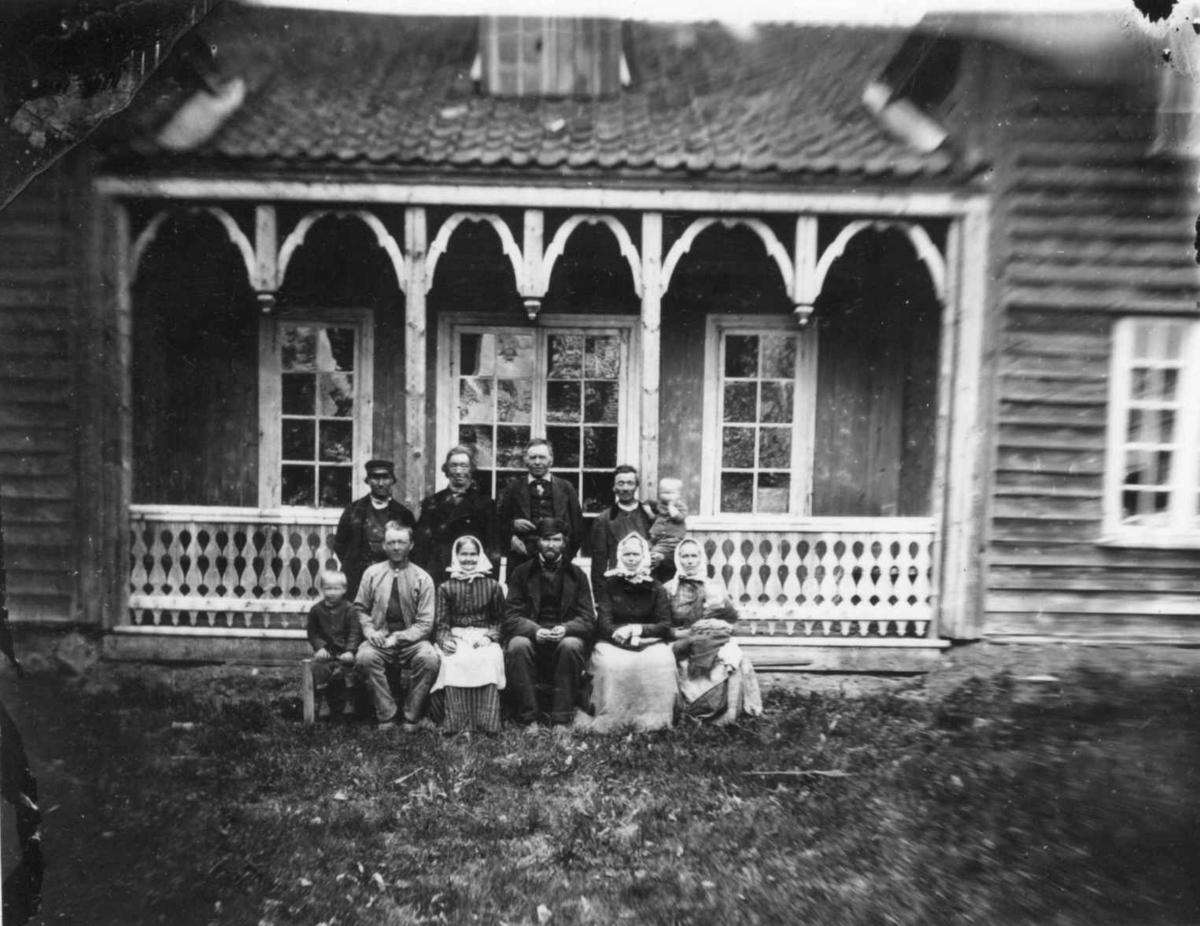 Husmannsfolk (ant.), Ullensaker. Gruppe barn og voksne poserer foran trebygning med søylerekke. Fra portrettserie av personer som bodde på eller besøkte Dal gård, Ullensaker, fotografert av gårdens eier, kammerherre Fredrik Emil Faye (1844-1903) i årene 1875-1900.