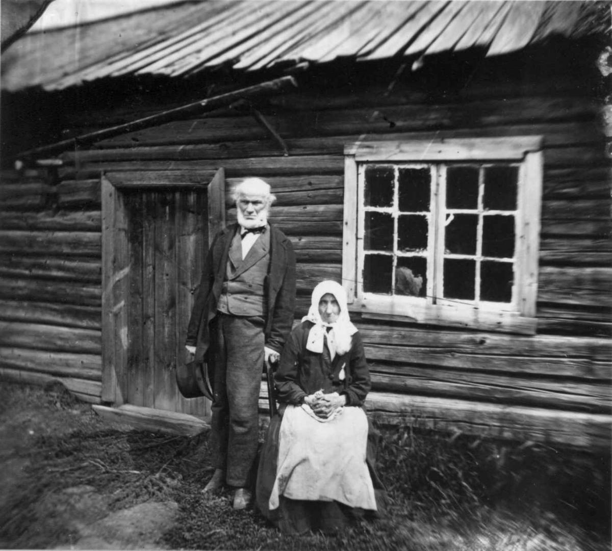 Husmannsfolk, Dal gård, Ullensaker. Eldre par poserer utenfor huset sitt, ca. 1879. Fra portrettserie av personer som bodde på eller besøkte Dal gård, Ullensaker, fotografert av gårdens eier, kammerherre Fredrik Emil Faye (1844-1903) i årene 1875-1900.